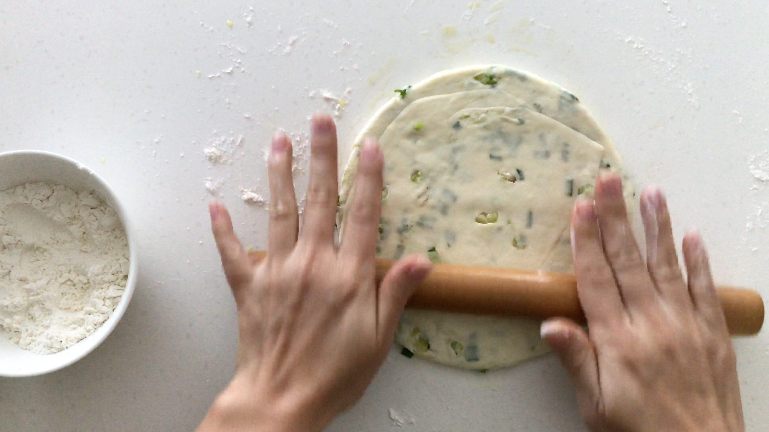 Flattening a scallion pancake with a rolling pin