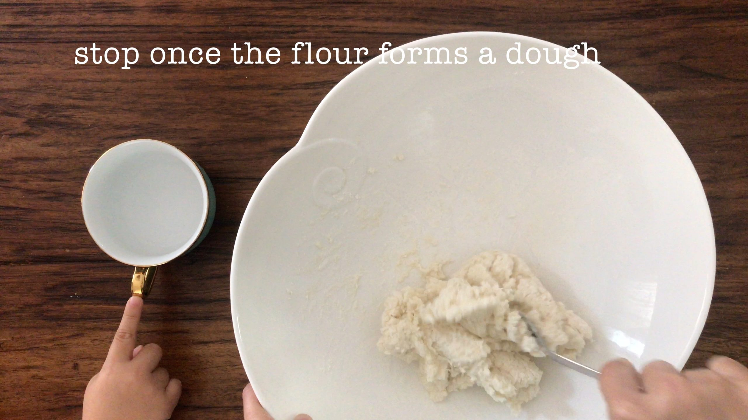 Using a fork to mix plain flour and hot water to form a dough in a big white bowl
