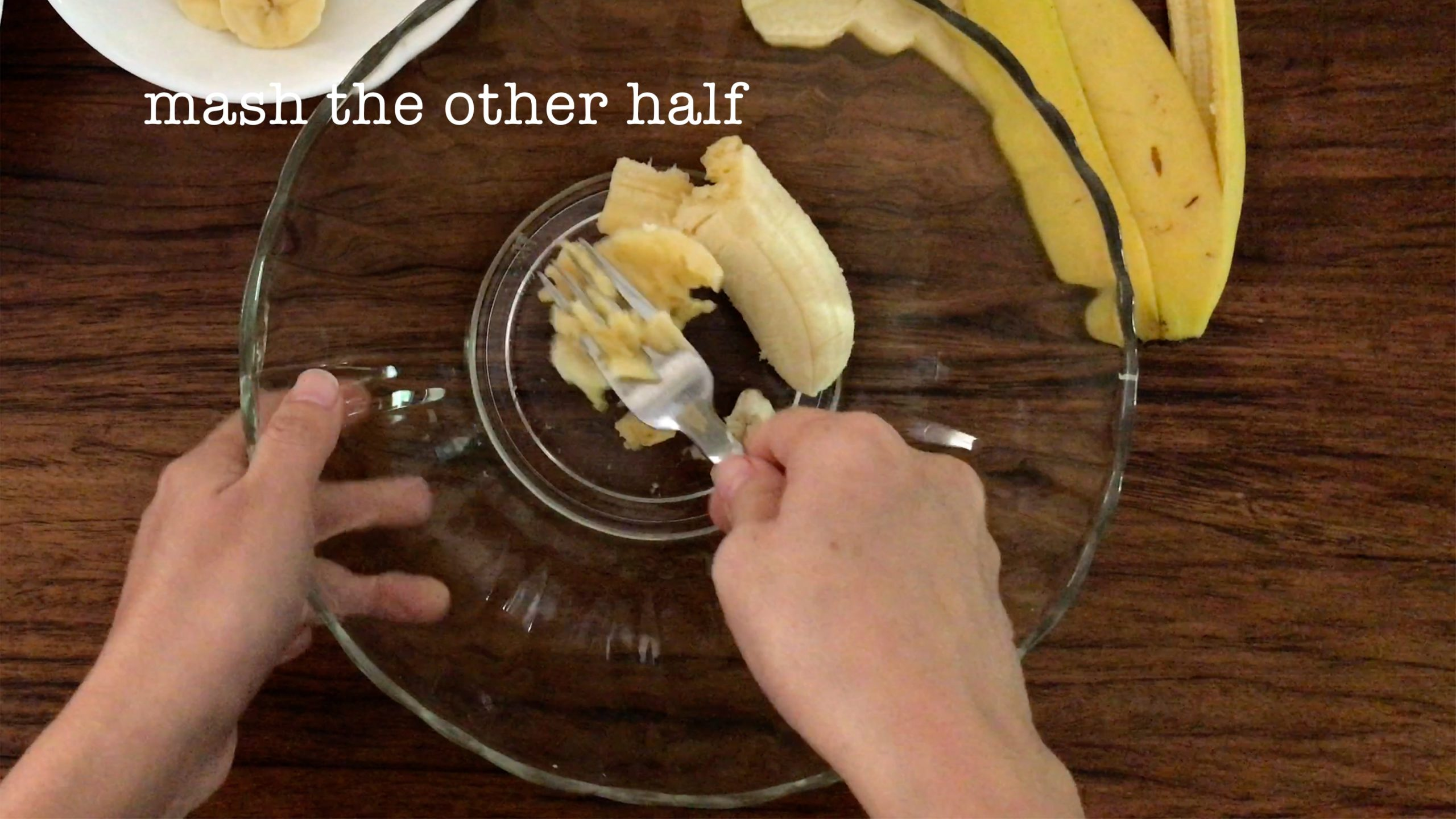 mashing half of a banana in a big glass bowl with a fork
