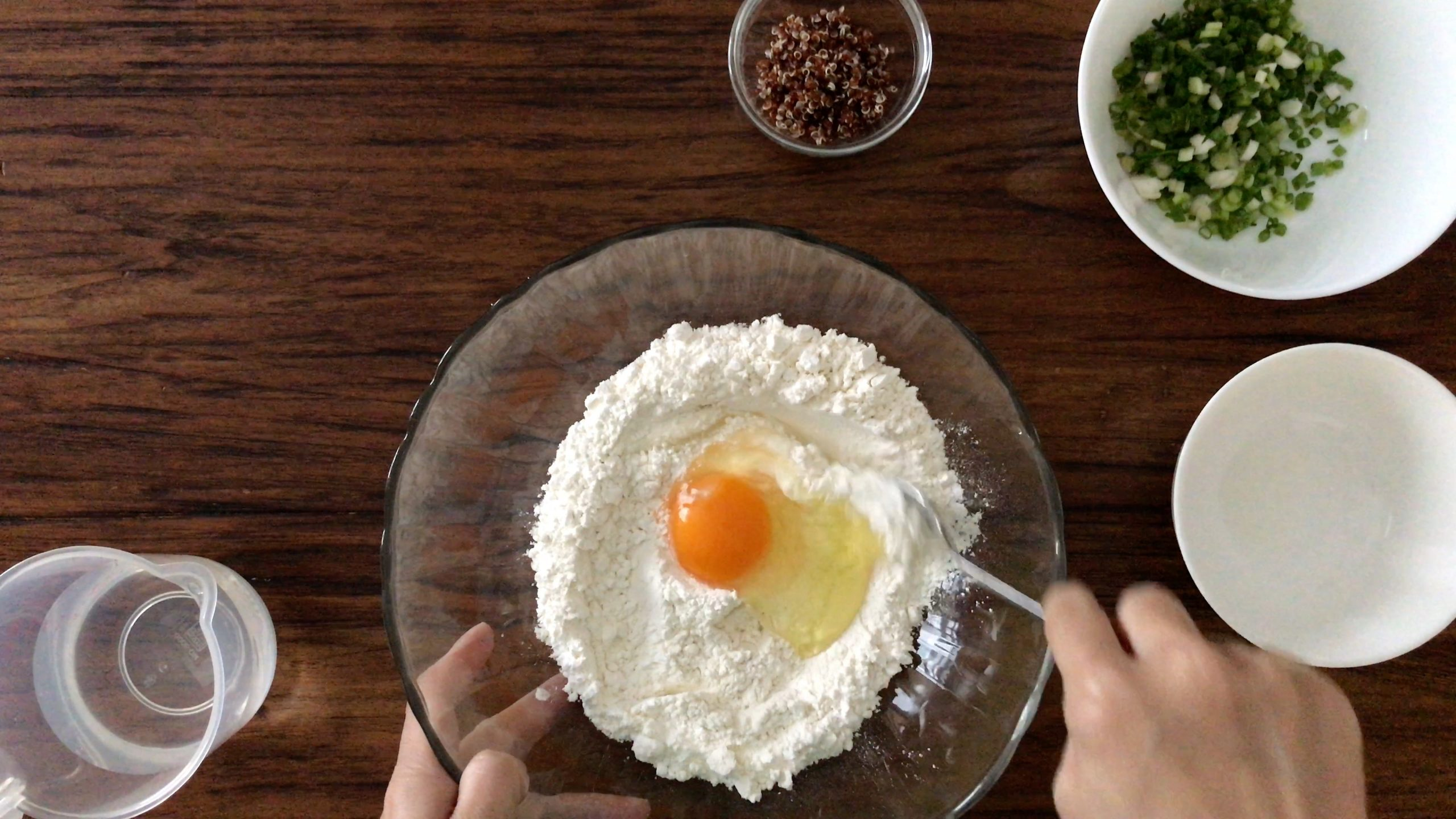 an egg sitting in the middle of some flour in a big glass bowl