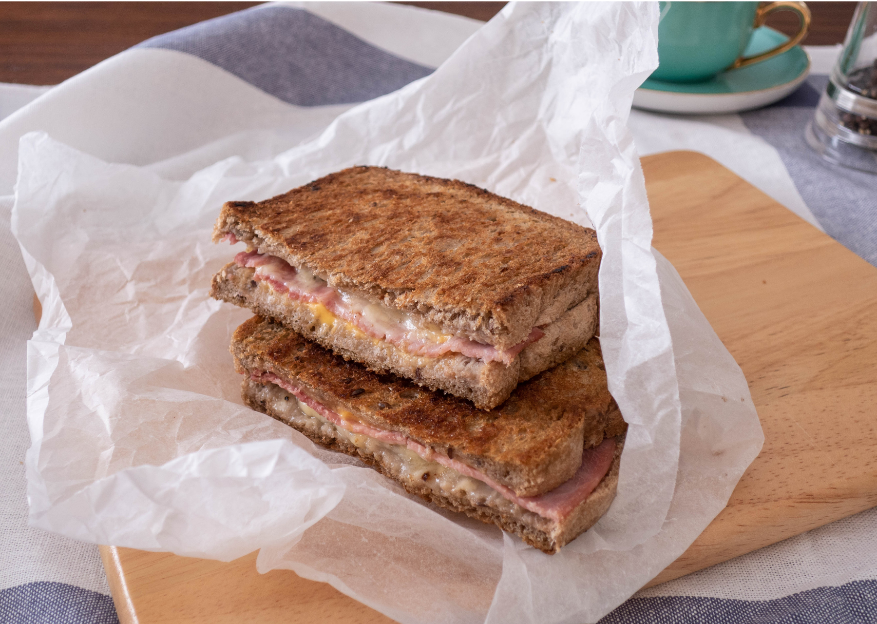 Halved grilled ham and cheese sandwich on a piece of baking paper