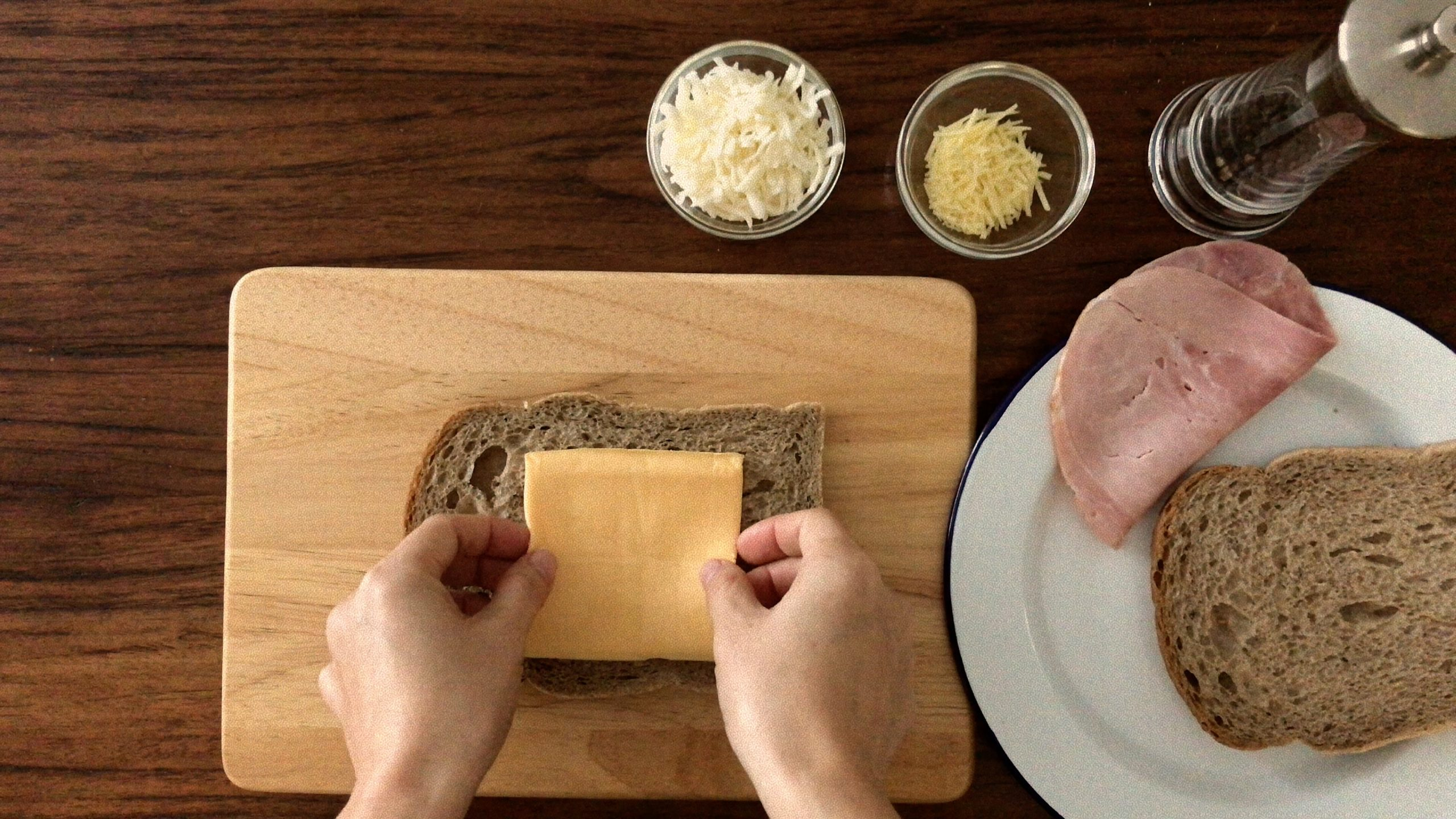 Putting a slice of Cheddar on a piece of brown break on a wooden board
