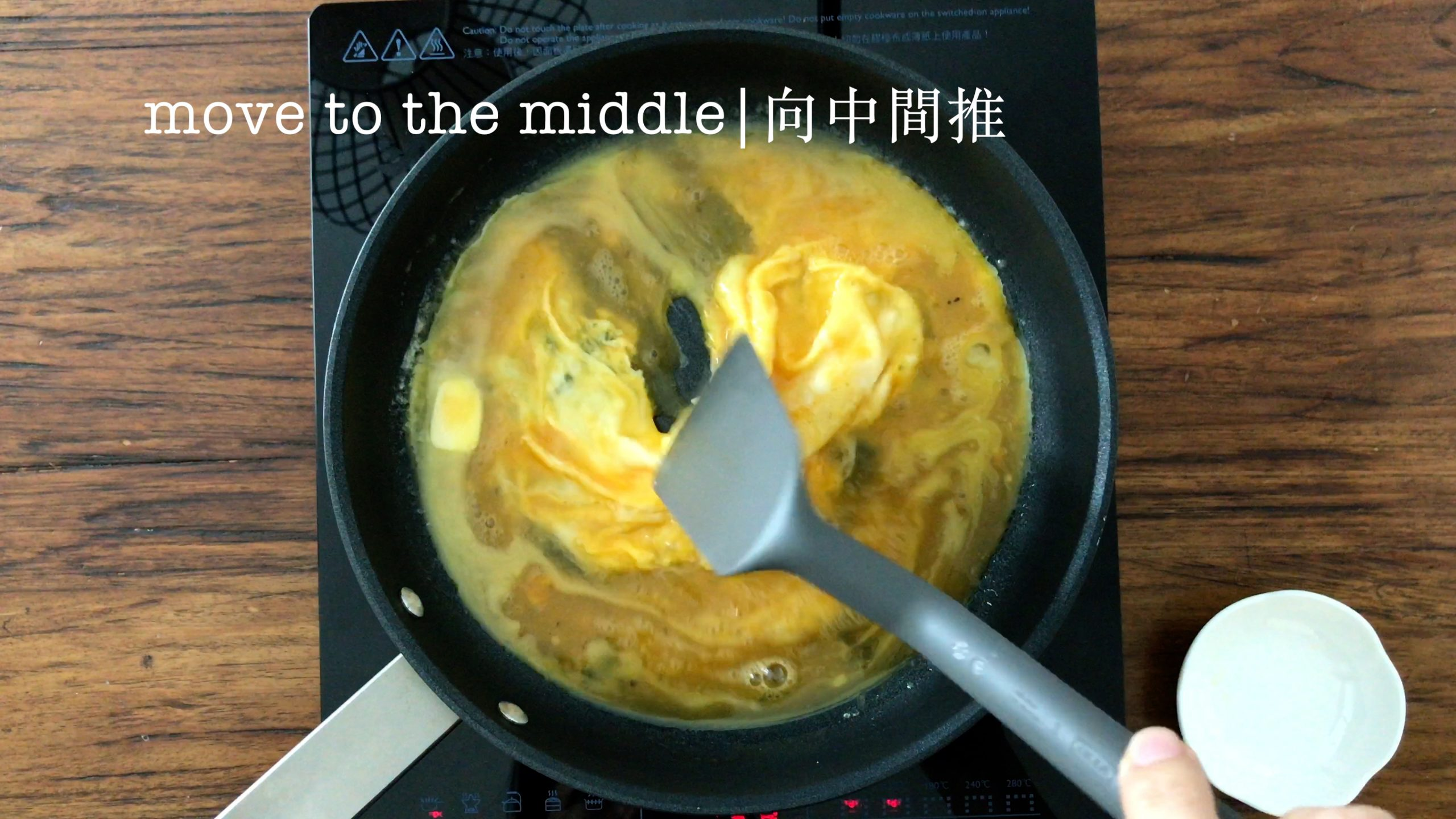 Using a grey spatula to move the egg mixed to the middle of a pan