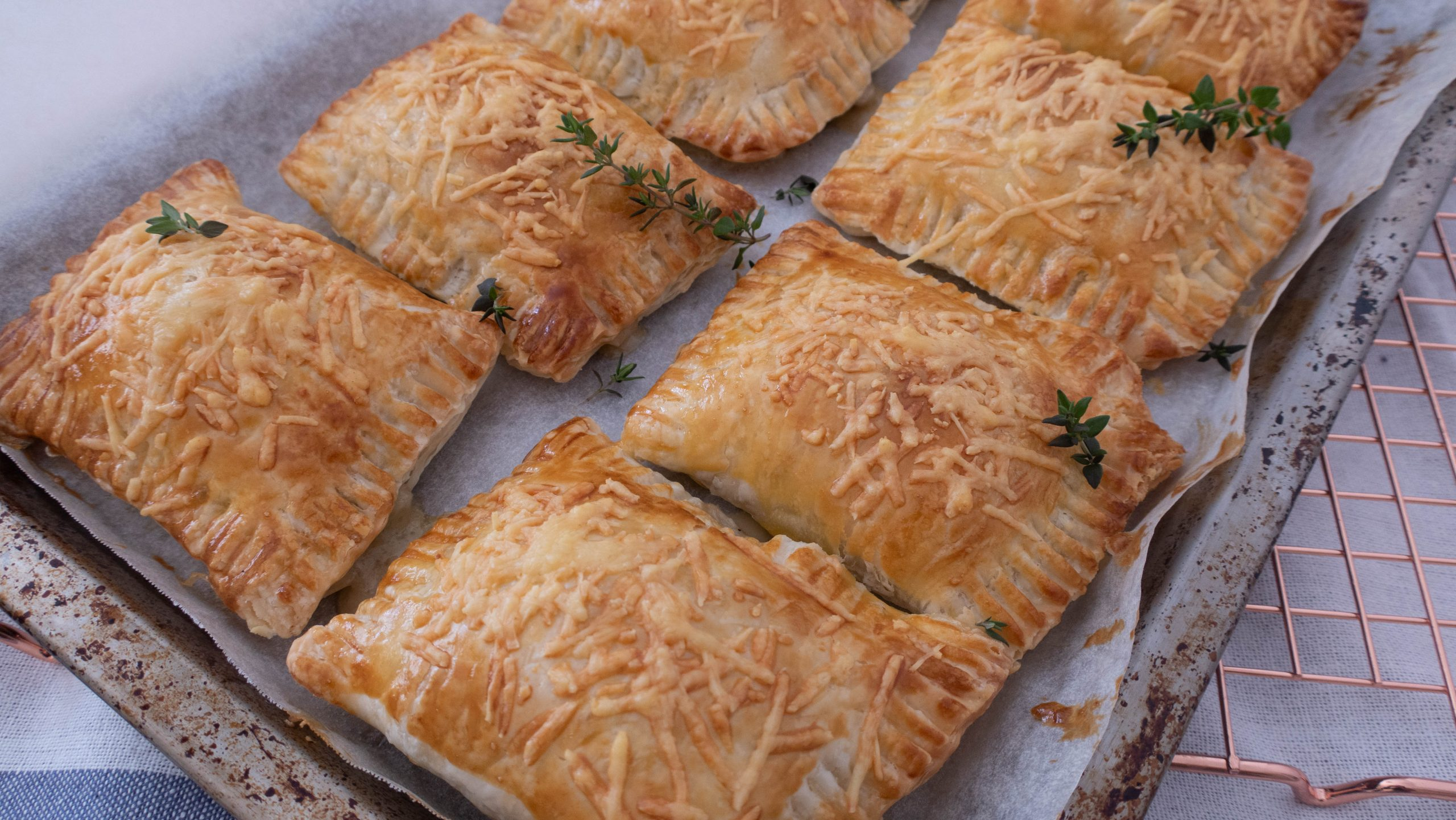 eight golden brown pastries garnished with fresh thyme in a baking tray on a rack